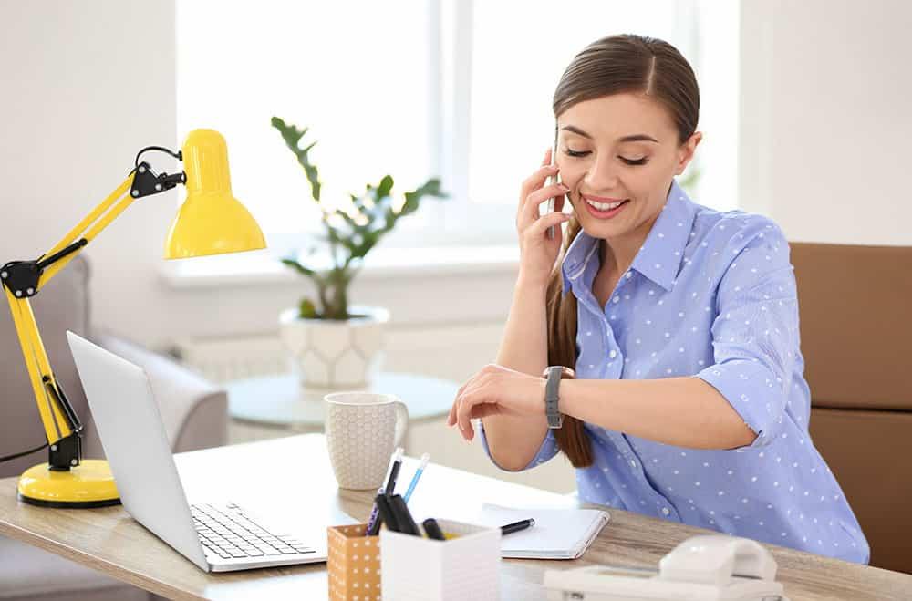 Junge Frau telefoniert bei der Arbeit und schaut auf die Uhr