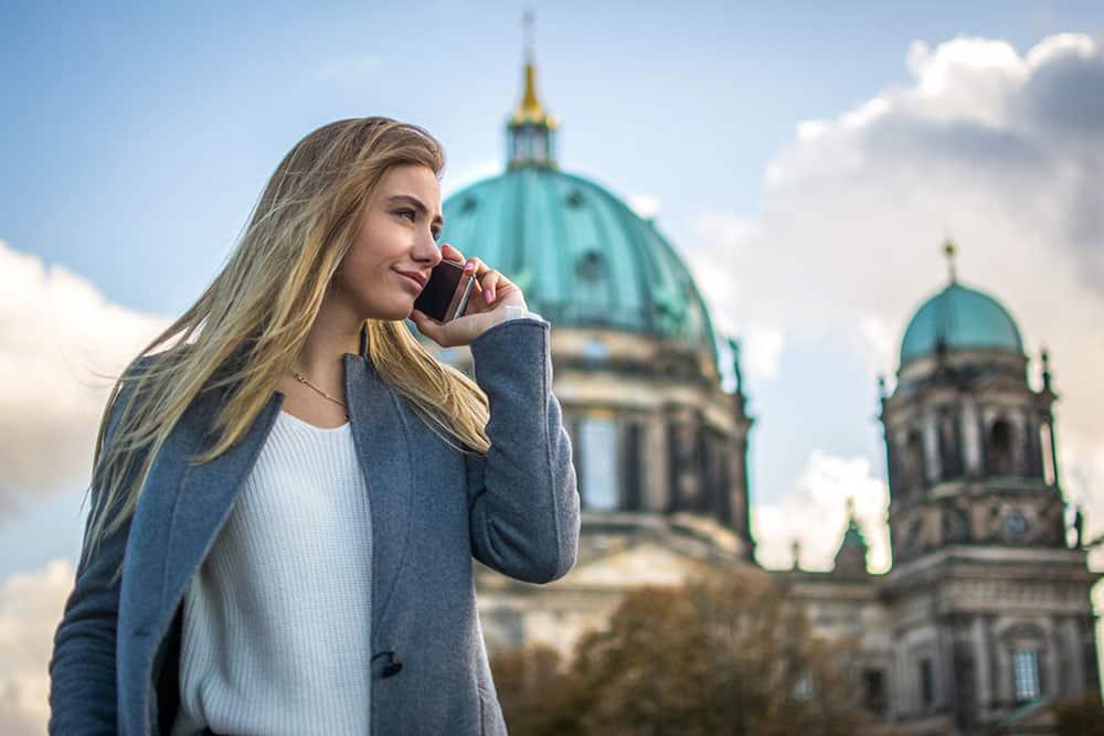 Junge Frau telefoniert vor dem Berliner Dom