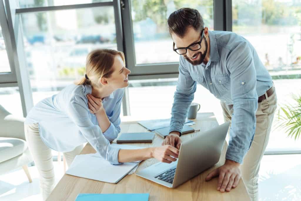 Zwei Kollegen schauen auf einen PC und sprechen