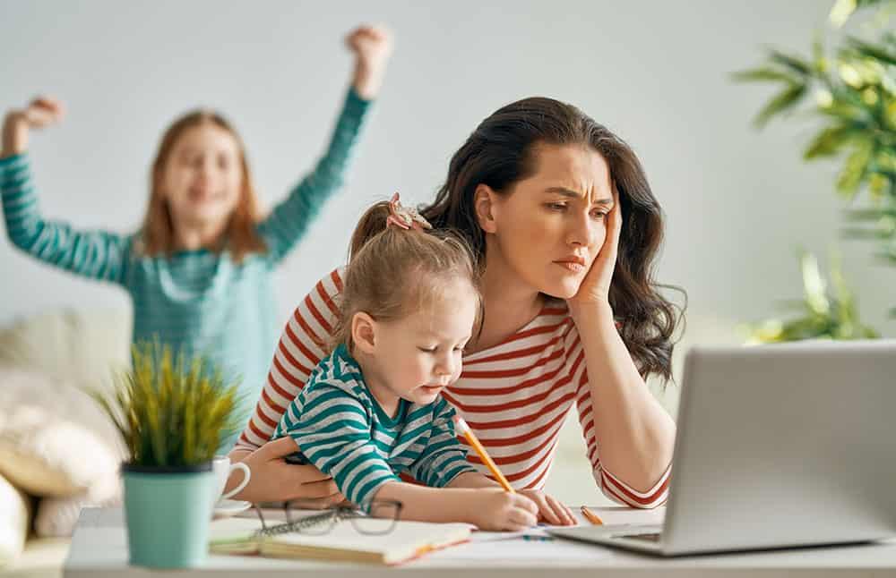 Junge Mutter sitzt müde am Laptop ein Kind sitzt auf ihrem Schoß ein anderen tanzt im Hintergrund